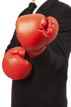 Businessman wearing black suit and red boxing gloves